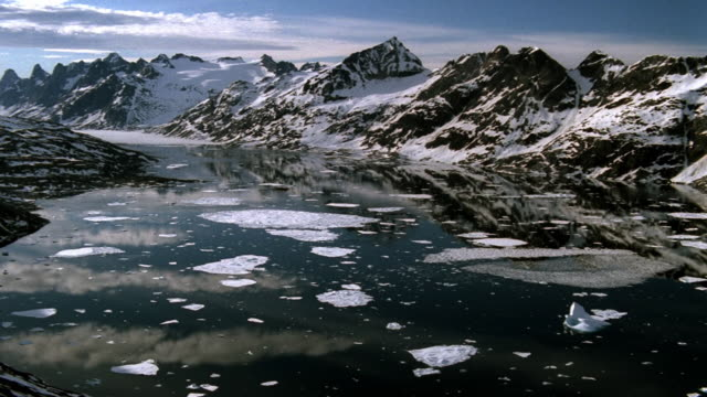 Aerial wide shot glaciers, water, and mountains / Greenland