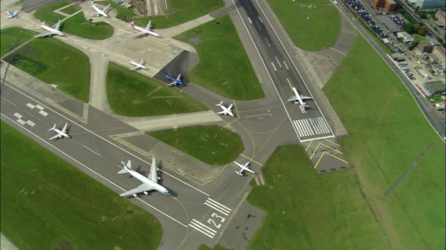 Aerial wide shot jets queued for takeoff at Heathrow Airport / pan zoom out Heathrow and horizon / London, England
