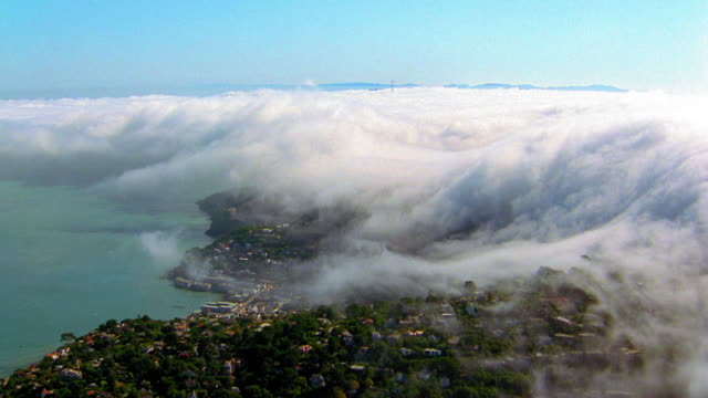 Aerial wide shot over residential area and town on coast with low rolling clouds or fog / California
