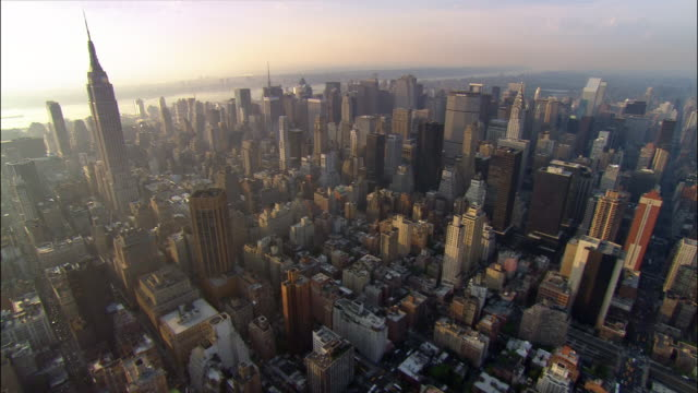 Aerial wide shot pan across midtown Manhattan east to west just south of Central Park/ New York, New York
