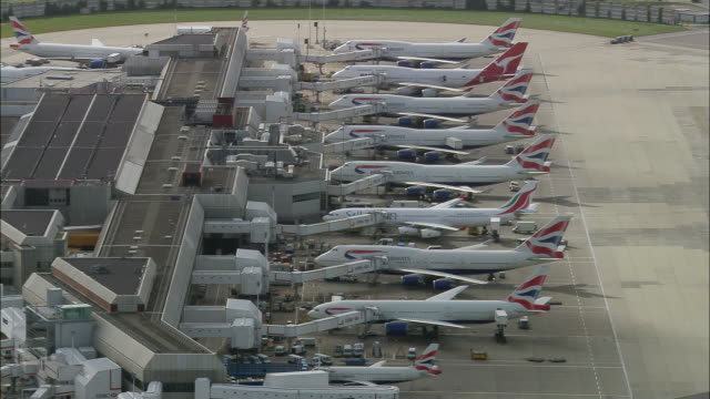 Aerial wide shot pan British Airways jets at Heathrow Airport gates / London, England