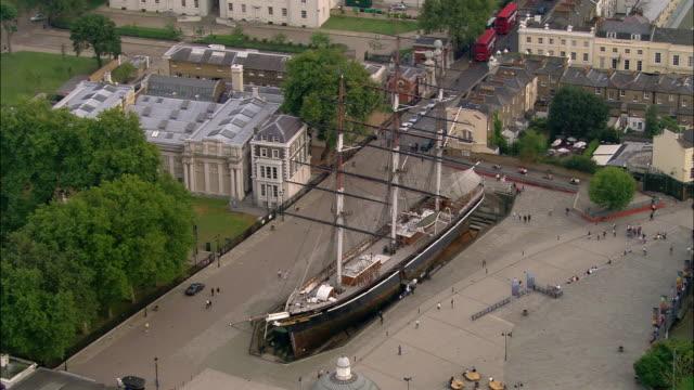 Aerial wide shot pan pedestrians walking in plaza surrounding Cutty Sark / Greenwich, London