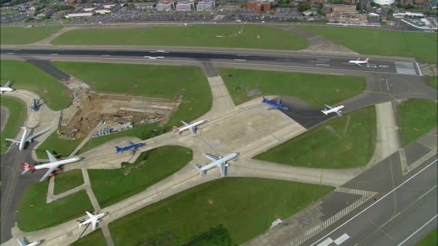 Aerial wide shot pan planes waiting to take off from Heathrow Airport / London, England