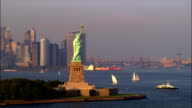 Aerial wide shot pan Statue of Liberty at sunset with sailboats in harbour and Lower Manhattan skyline in background/ New York, New York