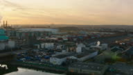 Aerial with helicopter over river to industrial area in the late afternoon