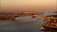 Aerial zoom in Bayonne Bridge/ pan over bridge down Kill Van Kull/ Staten Island, New York