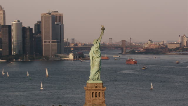 Aerial zoom out from Statue of Liberty to reveal lower Manhattan at end of day in NYC