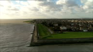 Aerials of Canvey Island Essex shore line and Thames Barrier ENGLAND Essex of London skyline from distance PULL OUT over Thames Estuary and Dartford...