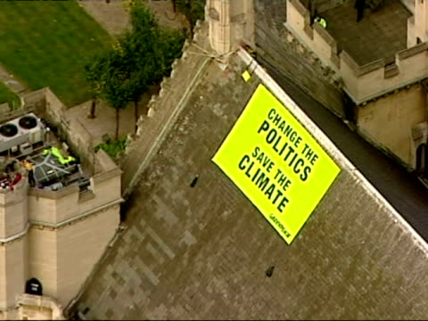 Aerials of Greenpeace banner and protesters on roof of Houses of Parliament