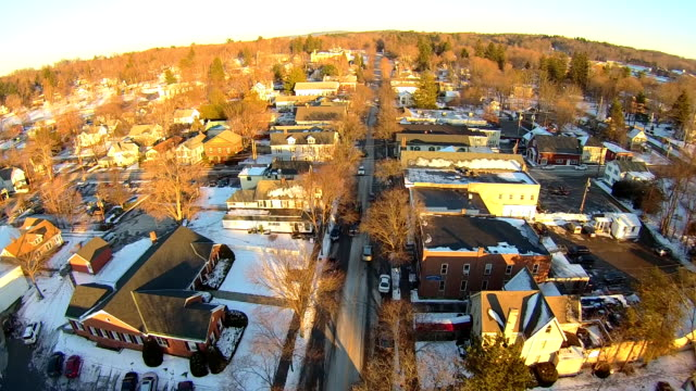 Aerials over a small New England town, cars below, afternoon, very clear cold day with golden light.