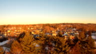 Aerials over a small New England town, trees, very clear cold day with golden light.