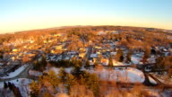 Aerials up high over a small New England town, afternoon, very clear cold day with golden light.