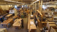Aeriel perspective of floor of large, custom woodworking shop with numerous work stations and workers visible