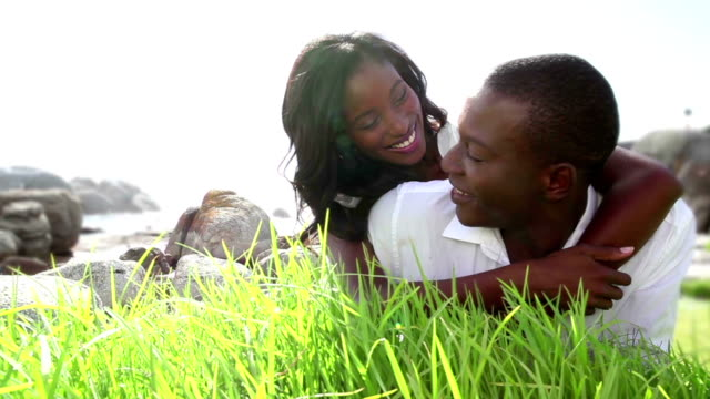 Affectionate couple lying on grass smiling