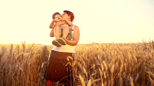 SLO MO Affectionate mother and son in field of wheat