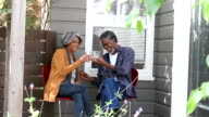 Affectionate senior African American man toasting glass with woman