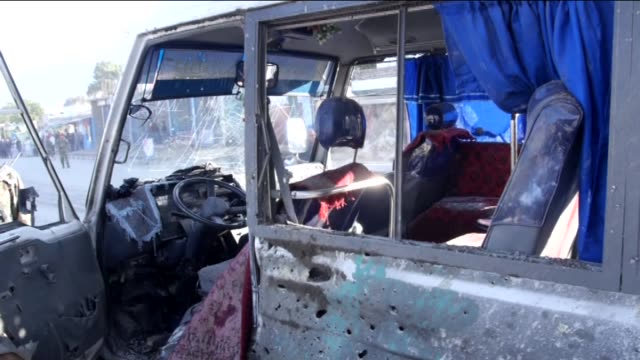 Afghan security forces take security measures near a minibus which is destroyed in a roadside bomb explosion in Kabul Afghanistan on October 21 2014...