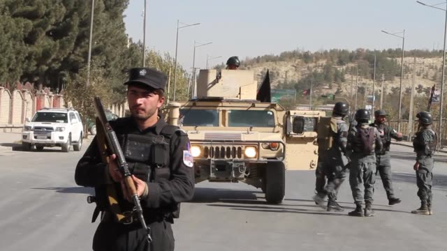 Afghan security officials take positions near the scene of an attack by armed men on Shamshad TV station in Kabul Afghanistan on November 07 2017 A...