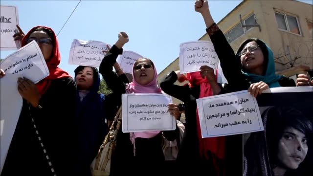 Afghan students and activists take part in a demonstration to support the Elimination of Violence against Women law in front of the Parliament in...