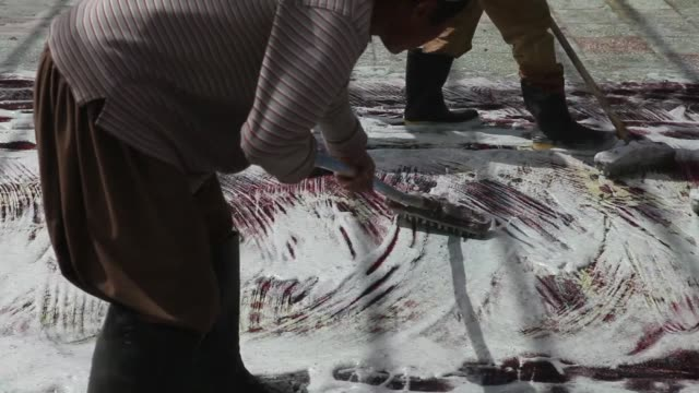 Afghan workers use soap and cleaners to scrub a finished rug at a facility to clean and trim hand made carpets in Kabul Afghanistan Workers wearing...