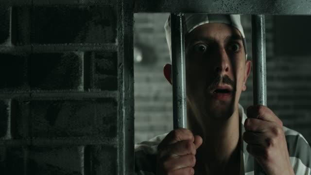 Afraid men holding prison bars at prison cell