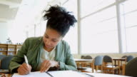 African American adult college student studying in brightly lit library