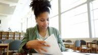 African American adult woman writing while studying in college library