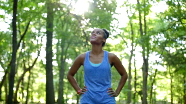African American athletic woman checking pulse while off road running