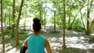 African American athletic woman is running off road in park