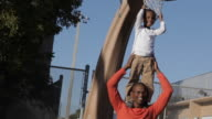 African American boy standing on father's shoulders