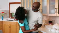 African American couple dancing in domestic kitchen