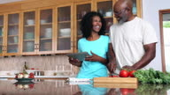 African American couple preparing food in kitchen using recipe on digital tablet