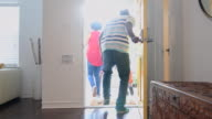 African American family leaving the house with front door open