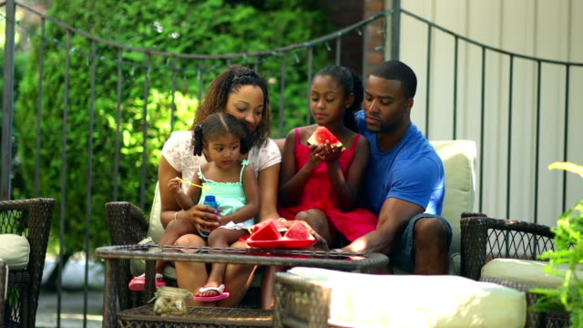 African American family outdoors on a couch together
