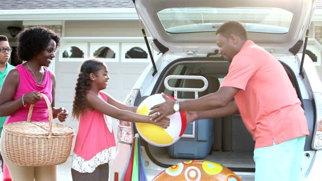 Afro-Amerikaanse familie verpakking auto voor reis naar beach