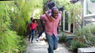 African American Family Piggy Backing Through the Garden