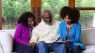 African American family sitting on sofa using digital tablet