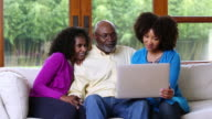 African American family sitting on sofa using laptop