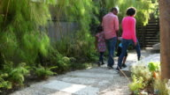 African American Family Walking Through the House Yard