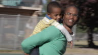 African American father carrying son on back