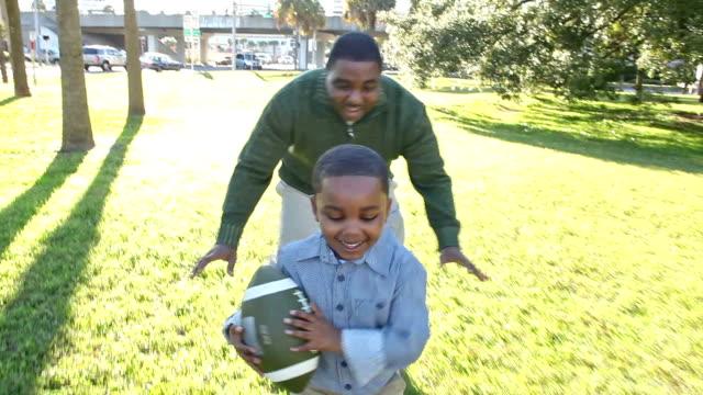 African American Vater mit kleinen Jungen und Fußball