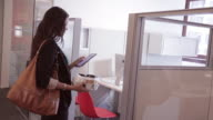 African American female executive stops to check her tablet before walking into cubicle in the morning