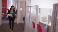 African American female executive walks through office looking at tablet and carrying coffees