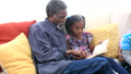 African American grandfather reading book to young girl on sofa