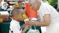 African American grandmother giving grandson orange juice