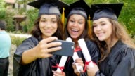 African American, Hispanic and Caucasian college friends take selfies after graduation
