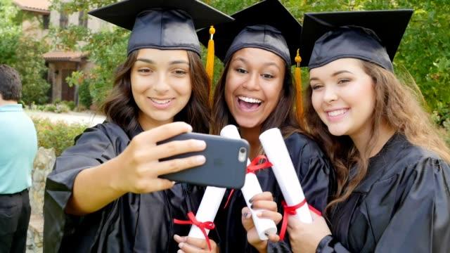 African American, de Hispanic en de Kaukasische college vrienden nemen selfies na afstuderen
