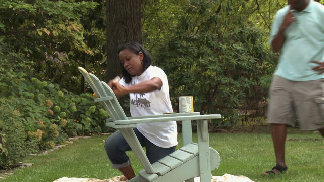 African American husband and wife painting wooden adirondack chair in yard