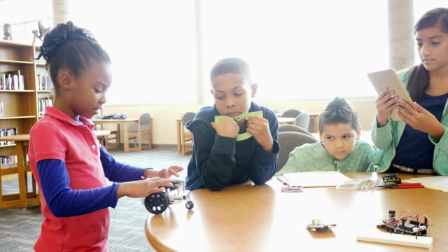 African American male mid-adult teacher supervise as elementary and middle school students work with robot
