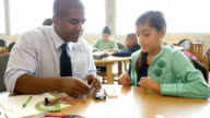 African American mid-adult teacher helps pre-teen student with electrical components